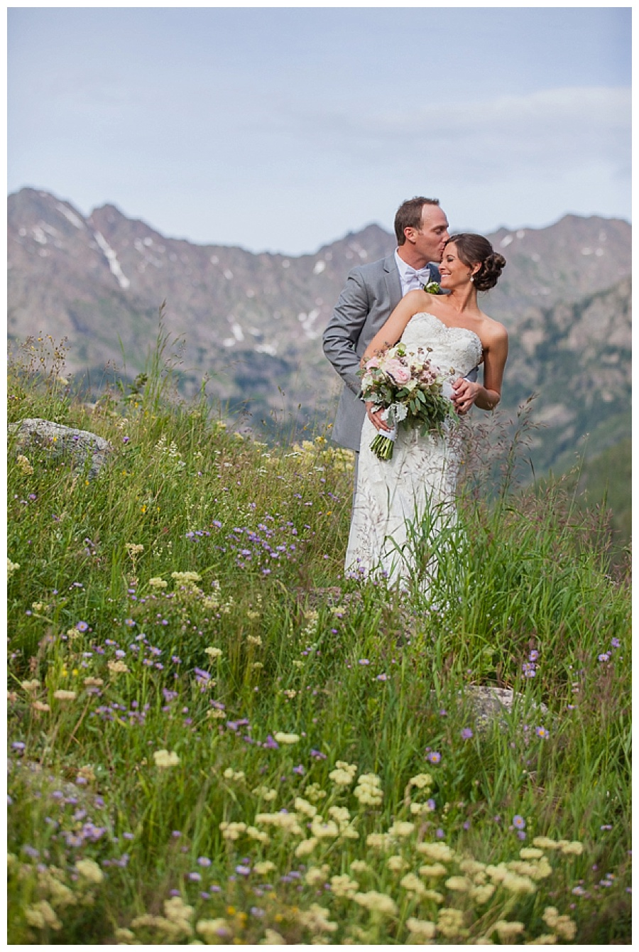 14 Bride and Groom on top of mountain with wild flowers Piney River Ranch