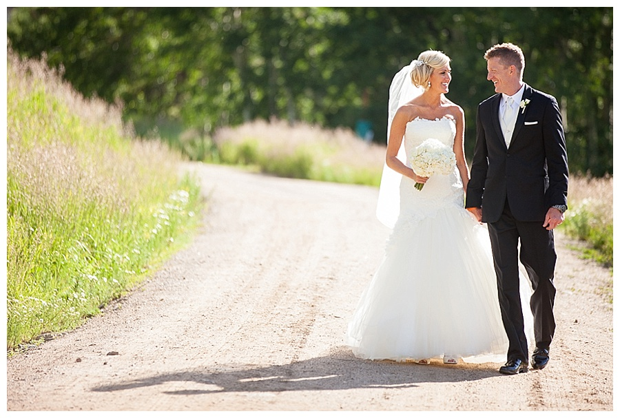25 Bride and Groom walking on dirt road in Beaver Creek Colorado