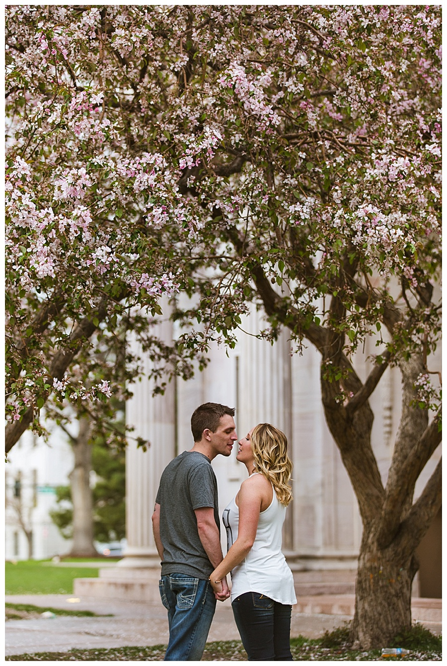 01 Downtown Denver engagement photos with blossoming trees in the rain